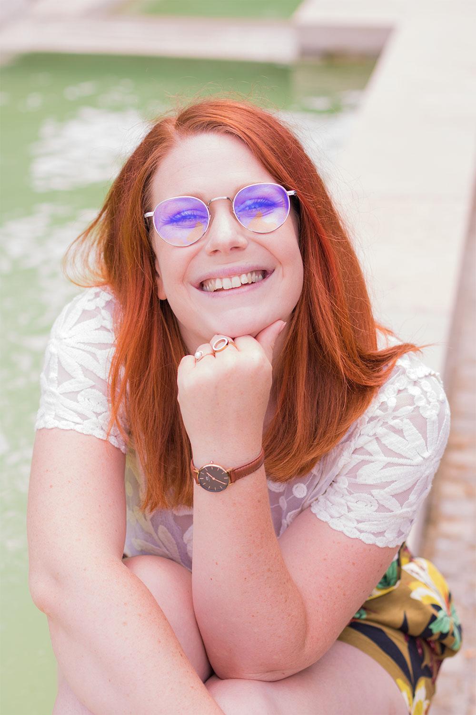 Portrait assise sur les bords d'une fontaine, le sourire au lèvres, en t-shirt dentelle blanc Zara