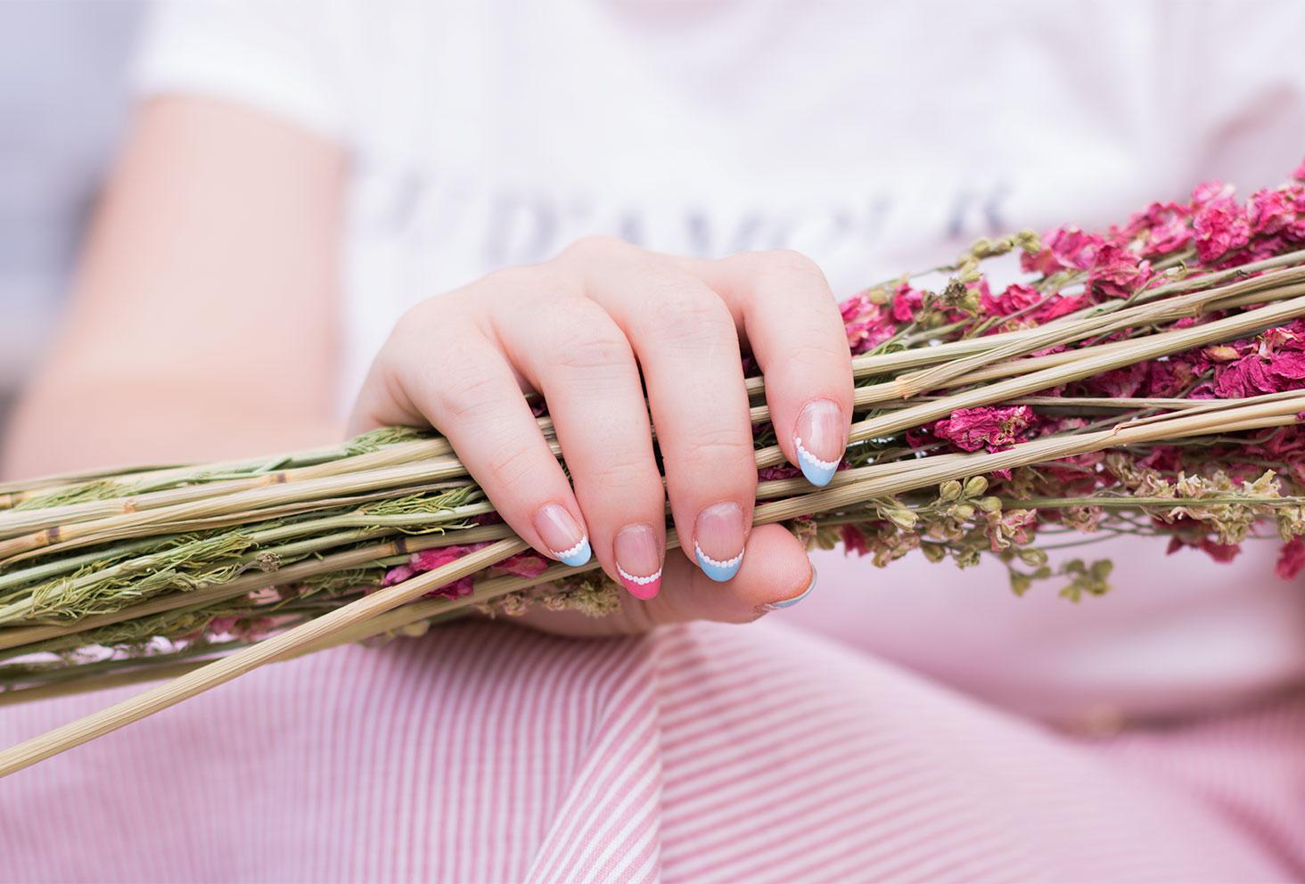 Zoom sur une french manucure tout en dentelle et pastel avec des fleurs séchées dans la main