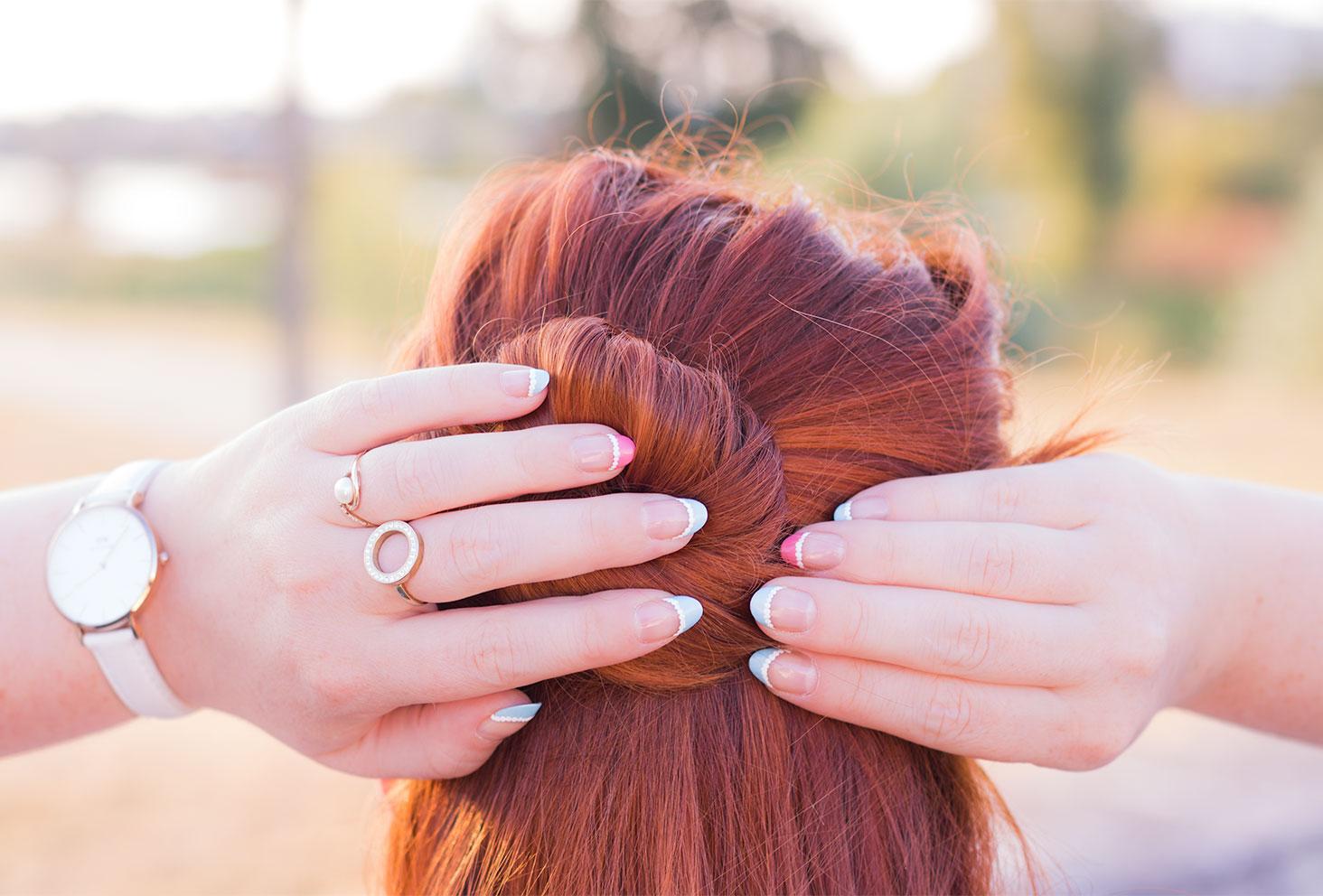Zoom sur le nailart d'une french manucure pastel-acidulée en dentelle, les mains dans les cheveux