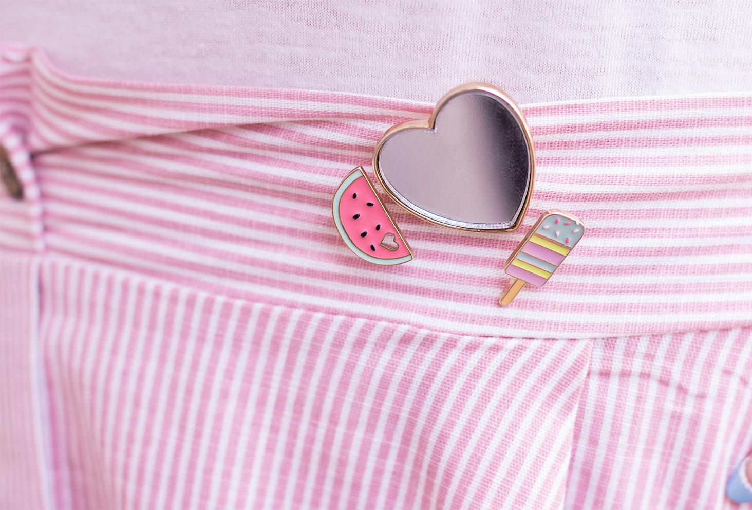 Zoom sur un pin's coeur miroir, un pastèque et une glace accrochés en haut de la jupe à rayures roses et blanches Shein