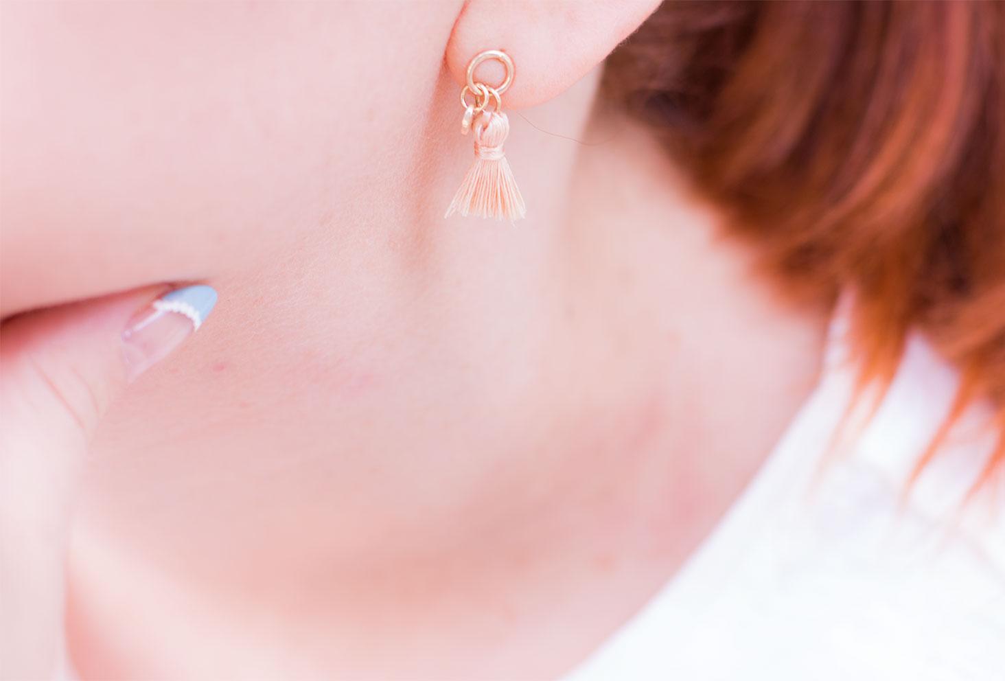 Zoom sur les petites boucles d'oreilles roses pastel à pompons Kiabi portées