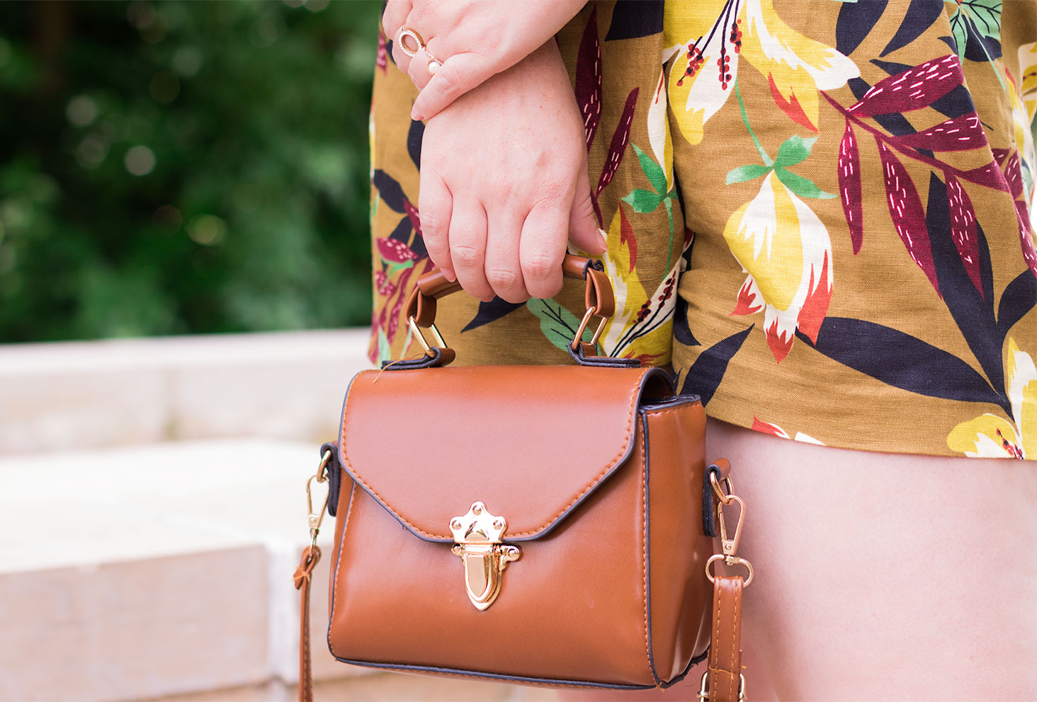 Zoom sac camel Shein, tenu dans la main devant un short à fleurs Zara