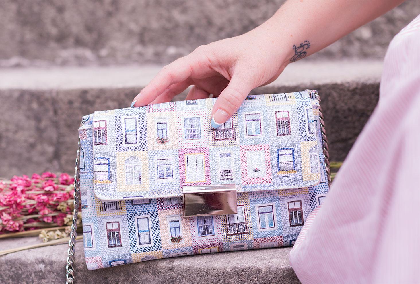 Zoom sur le sac à motifs maison pastel de Parfois posé sur des marches en pierre et tenu dans une main