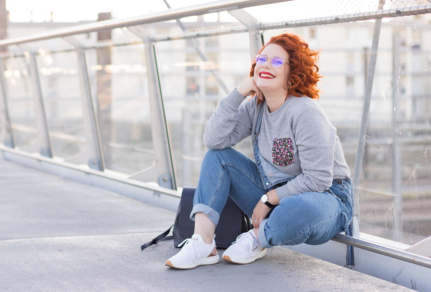 Assise en look street le long d'une rambarde en métal, le cheveux bouclés et le sourire aux lèvres
