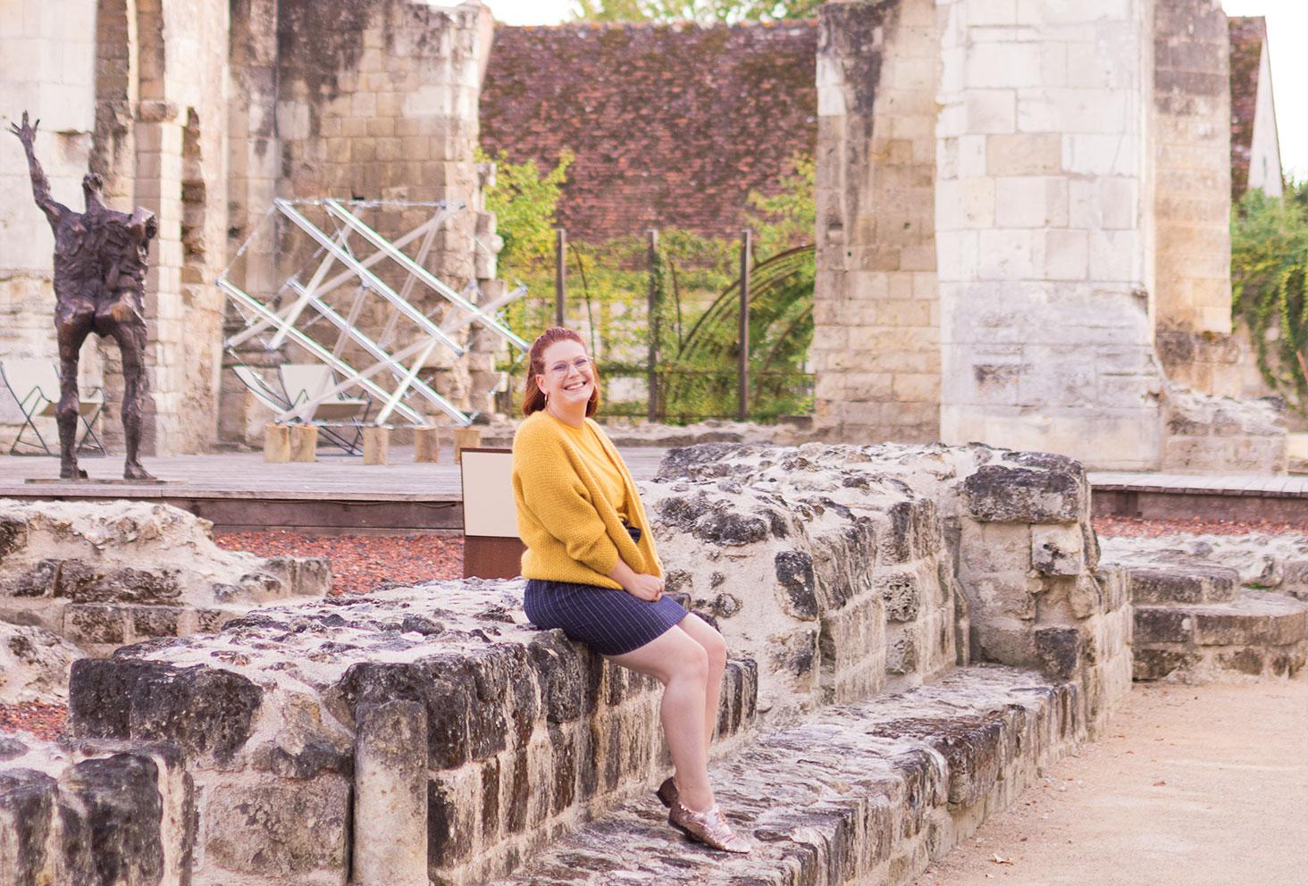 Assise au milieu des ruines en pierre, en jupe et derbies brillantes