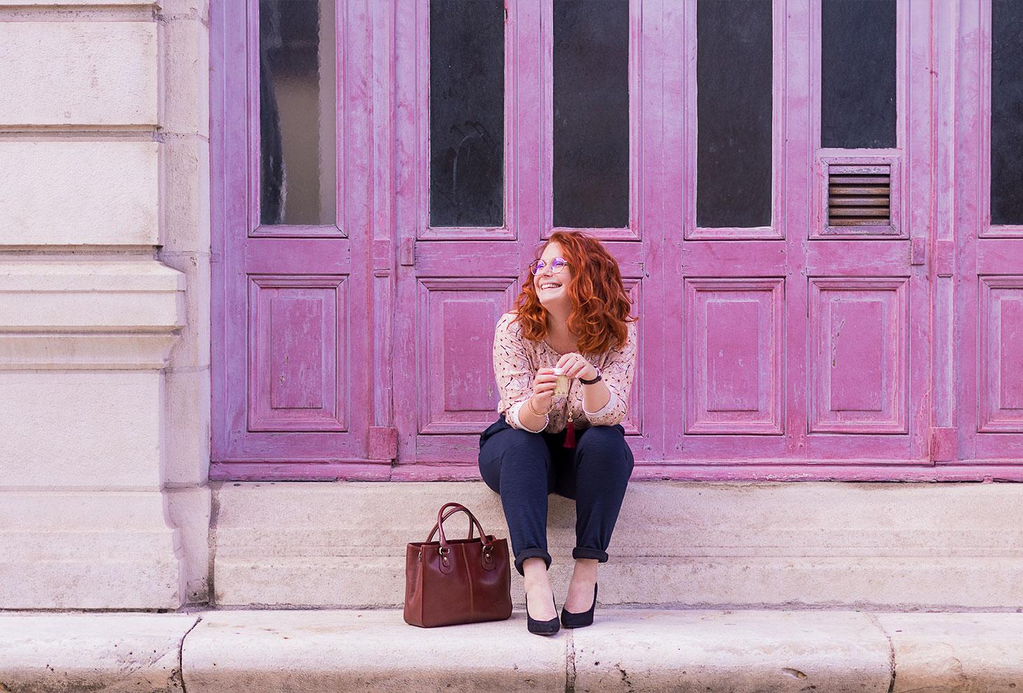 Assise sur les marches en pierre du grand théâtre de Tours, devant les portes vintages roses, en total look de working girl