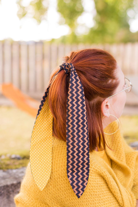Zoom sur le bandeau attaché en demi queue dans les cheveux, de dos avec un gros gilet jaune