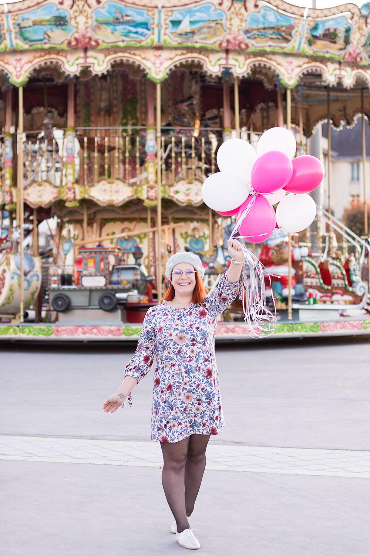 Happiness avec des ballons roses tendu en l'air à bouts de bras devant un carrousel lumineux