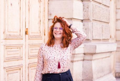 Le sourire aux lèvres, en blouse La Morue, la main dans les cheveux roux bouclés
