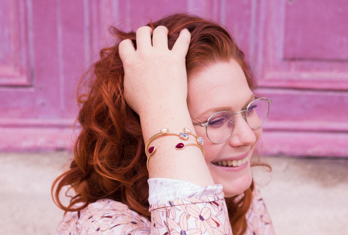 La main dans les cheveux, devant une porte rose, zoom sur les bracelets dorés MOA Paris