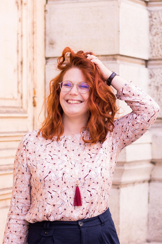 Portrait en blouse La Morue rose à fleurs, sautoir à pompon MOA, la main dans les cheveux bouclés et le sourire aux lèvres
