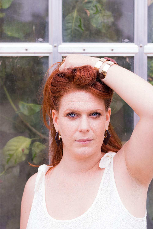 Photo portrait de face, très sérieuse, les cheveux relevés dans la main devant une verrière