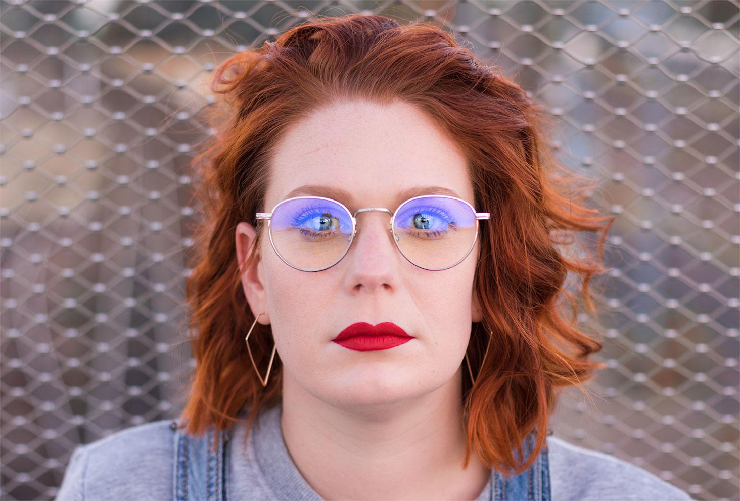 Portrait street, avec rouge à lèvres rouge et boucles d'oreilles géométriques, devant un grillage