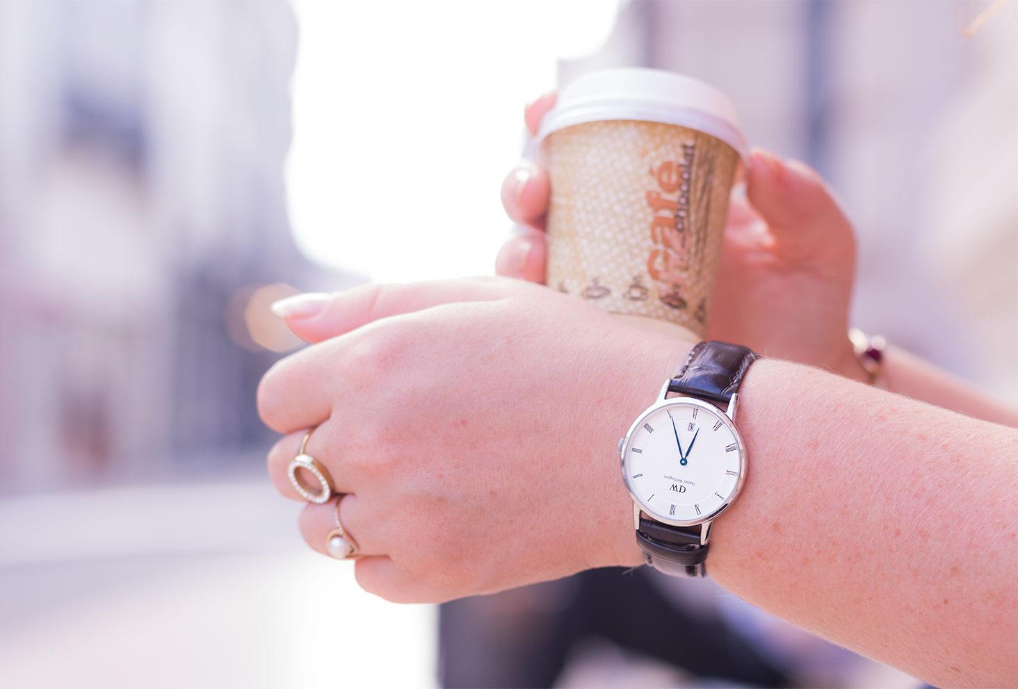 La montre marron Dapper Work de Daniel Wellington portée avec un café à emporter dans la main