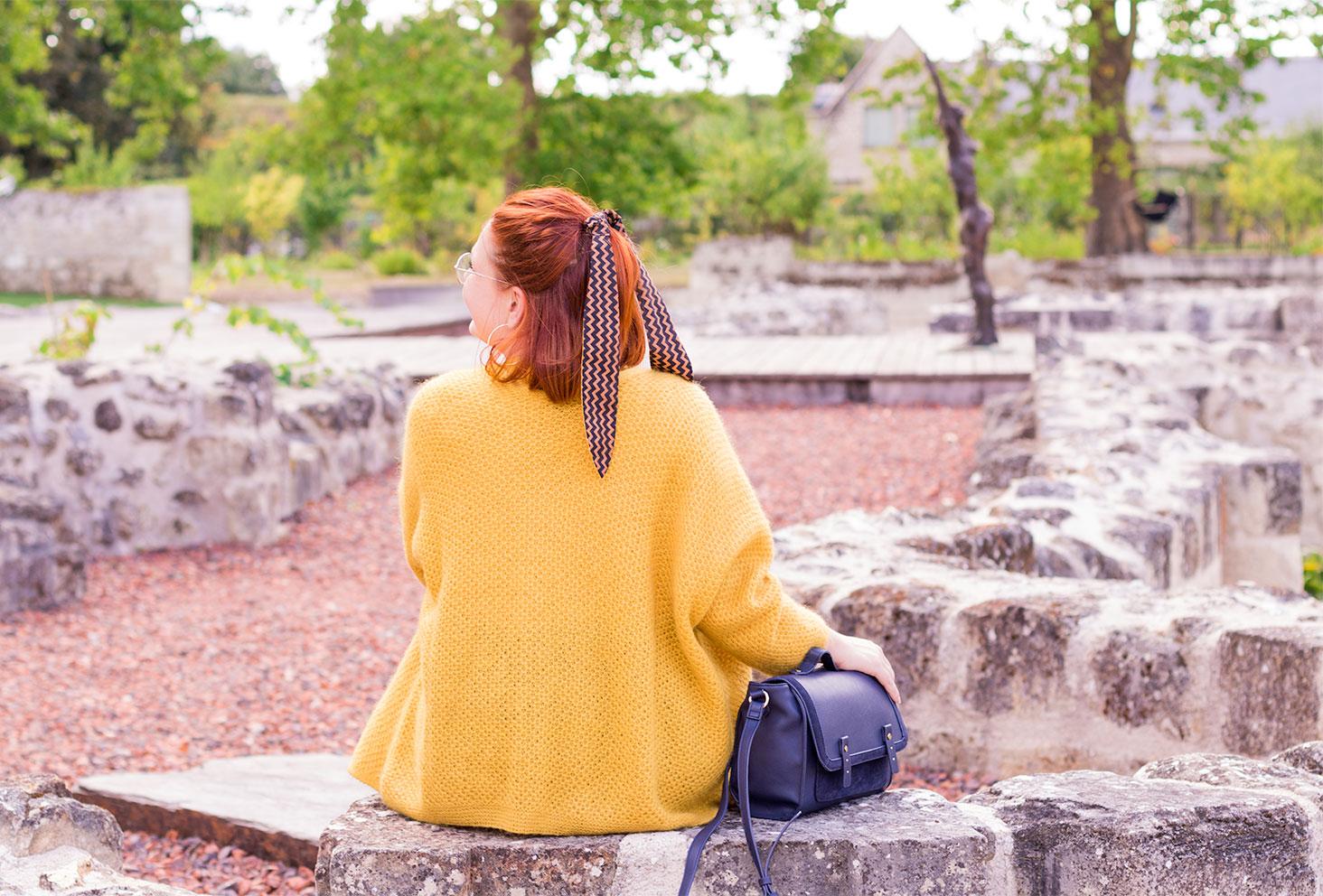 Assise de dos au milieu des ruines en pierre, en gilet jaune