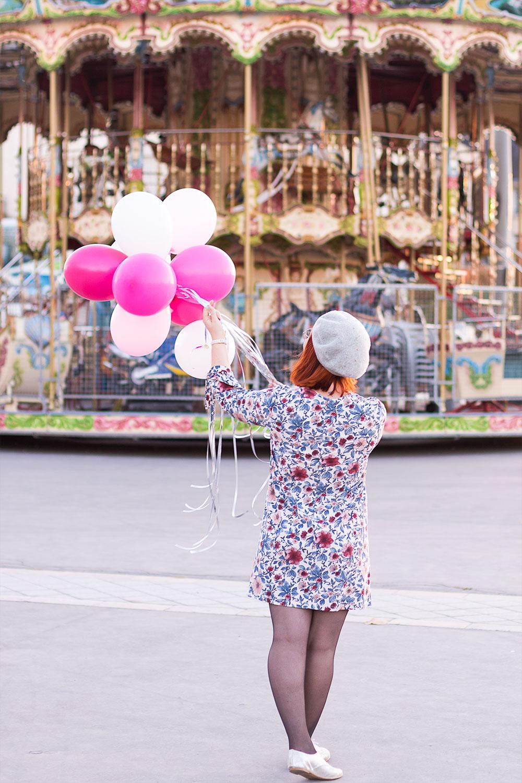 En entière de dos, des ballons dans les mains volant au dessus, devant un carrousel lumineux
