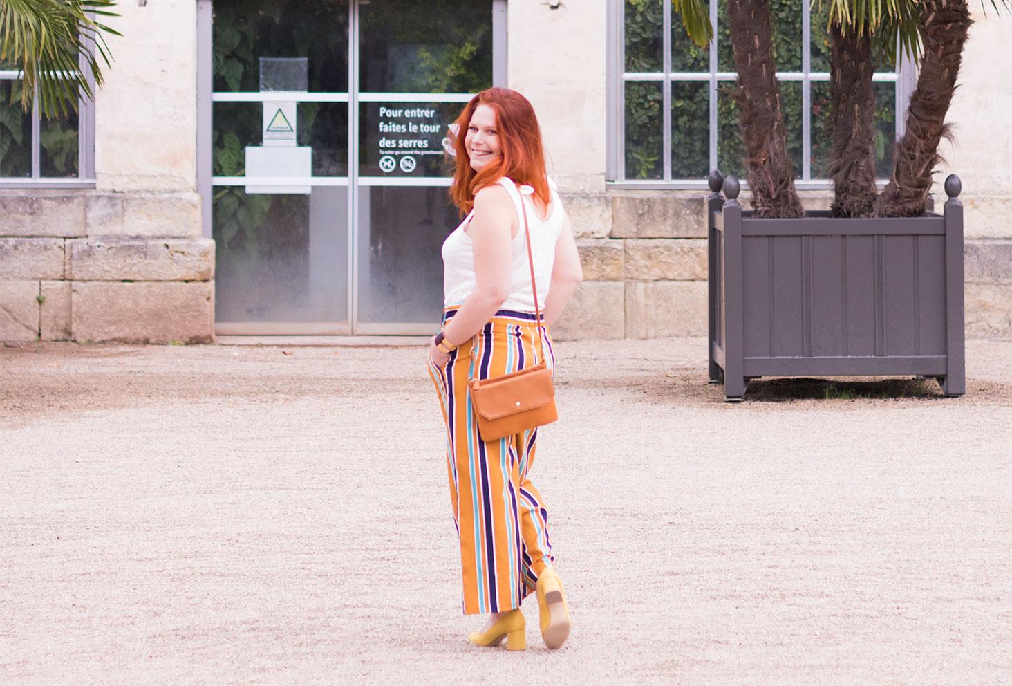 De dos, devant la verrière du jardin Botanique de Tours, en pantalon à rayures jaunes et bleus