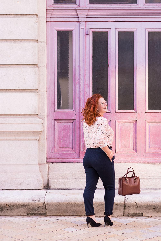 En entière de dos, devant les portes roses du grand théâtre de Tours, sur des escarpins hauts noirs et pantalon cigarette bleu marine, le sac posé aux pieds