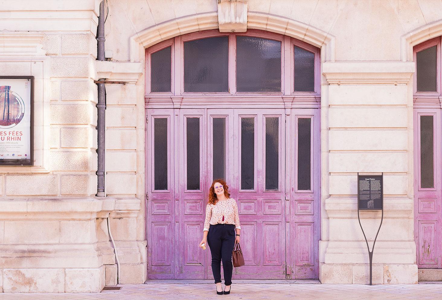 En look de working girl, pantalon cigarette et escarpins à talons hauts, devant les grandes portes en bois roses de l'opéra de Tours