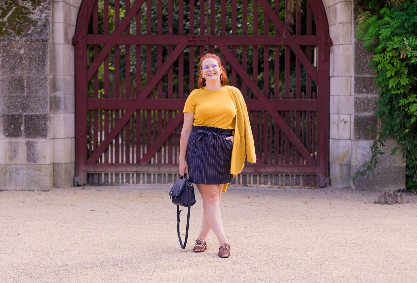 Devant un grand portail bordeaux en jupe bleu, t-shirt jaune et derbies à sequins, le sac dans la main