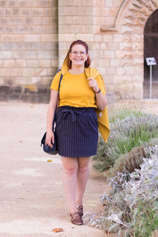 Devant une vieille bâtisse en pierre blanche, en t-shirt jaune et jupe cintrée bleue