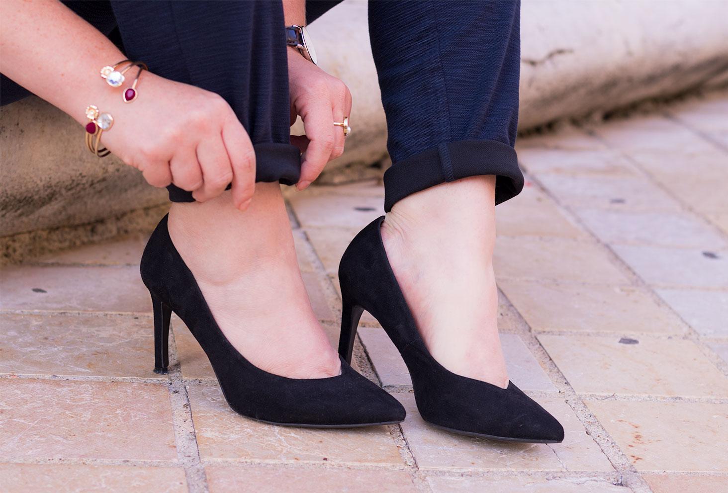 Zoom sur les escarpins noirs à talons hauts de la marque Kiabi portés, avec un pantalon cigarette confortable bleu marine