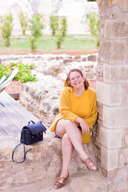 Assise dans une fenêtre en pierre, en gilet jaune et derbies à sequins, le sac cartable bleu posé à côté