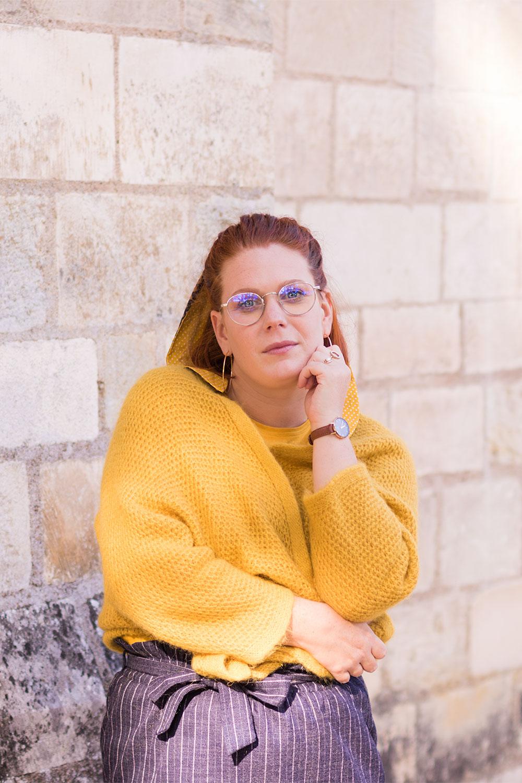 De face en gilet jaune et jupe bleue devant un mur en pierre