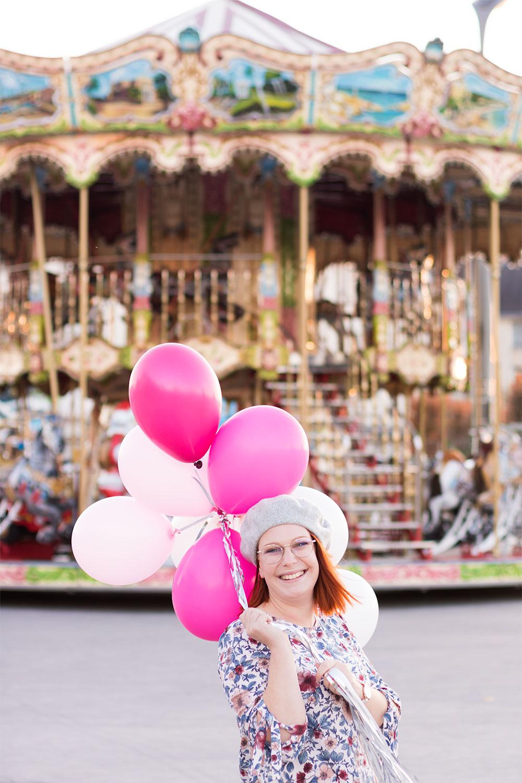 Devant un carrousel, des ballons roses dans les mains et le sourire aux lèvres, dans une robe fleurie aux mêmes couleurs des ballons