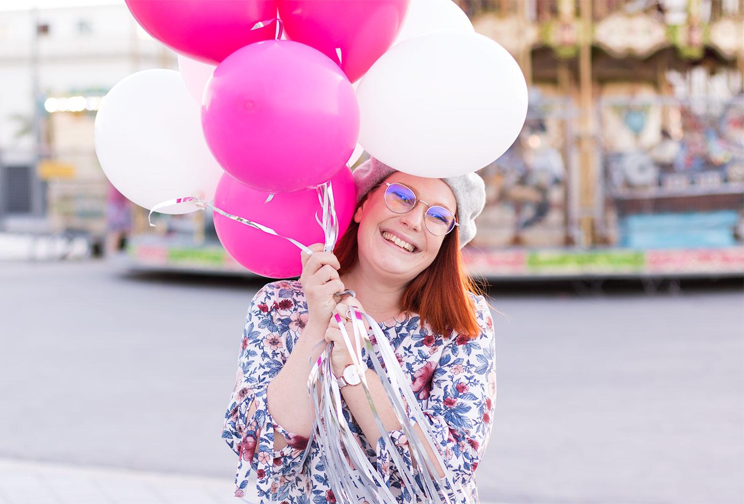 Zoom sur les ballons roses et blancs dans les mains, le sourire au lèvres en robe à fleurs, pour fêter la 27ème années