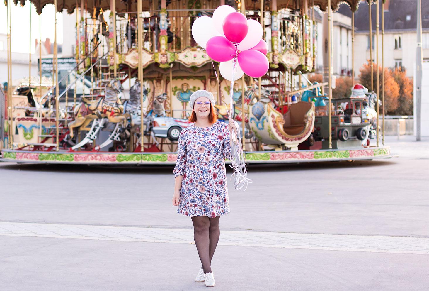 En balade devant un carrousel lumineux, en robe à fleurs, des ballons dans les mains pour son 27 ème anniversaire