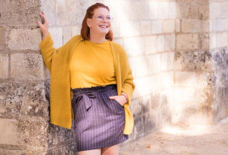 Accoudée le long d'un mur en pierre blanc, en jupe bleue et gilet jaune