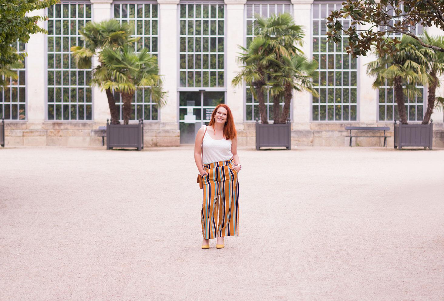 Look de rentrée entier devant les palmiers, en débardeurs blanc et pantalon à rayures fluide jaune, avec le sourire