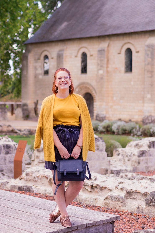 Debout sur une estrade en bois, en jupe et gilet devant une ancienne bâtisse en pierre, tenant le sac dans les mains devant le gilet simplement posé sur les épaules