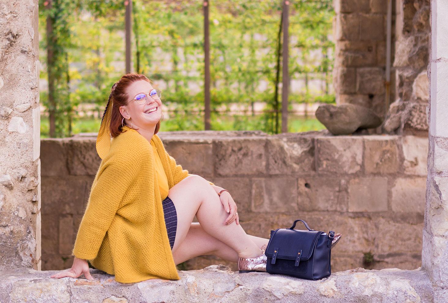 Assise dans une ouverture des ruines en pierre, en gilet jaune et derbies brillantes, de profil