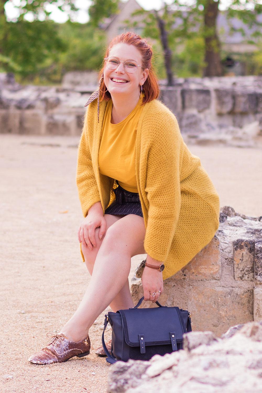 Assise sur un mur en pierre, en jupe entrain de ramasser le cartable au sol à côté des derbies à sequins
