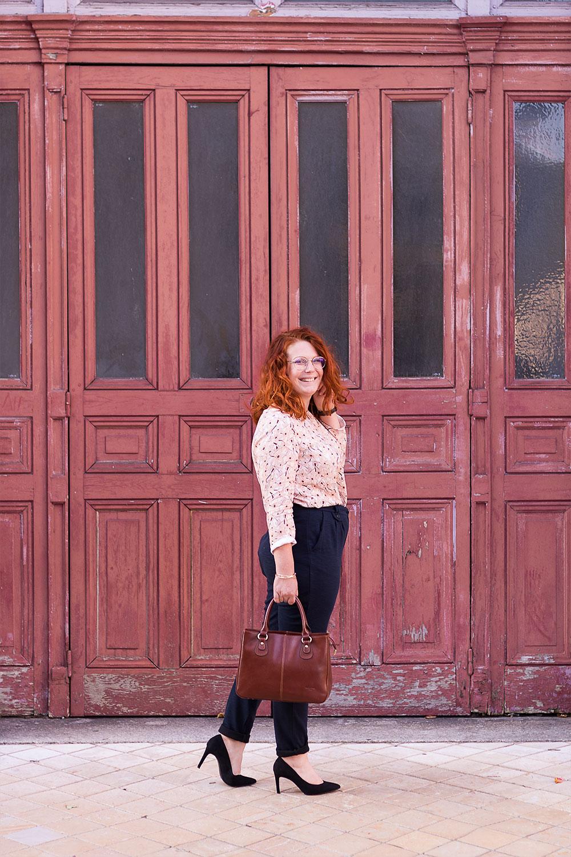 De profil devant une vieille porte en bois orange, en style working girl, blouse fluide La Morue et pantalon cigarette confortable, talons et sac en cuir dans la main
