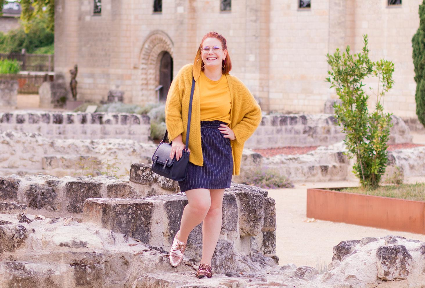 Debout sur un mur en pierre au milieu des ruines, en gilet jaune et jupe bleu à rayures