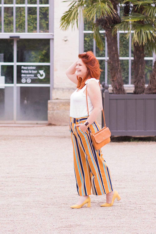 De profil, look en pantalon fluide et escarpins jaune , la main dans les cheveux en entier devant les palmiers