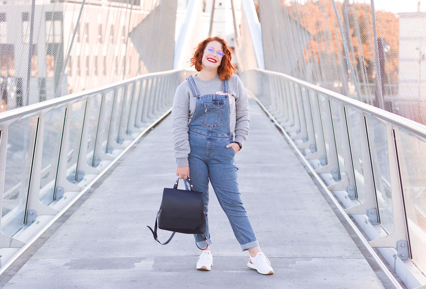En look street, salopette en jeans et baskets, au milieu d'une passerelle au dessus des lignes de chemins de fer