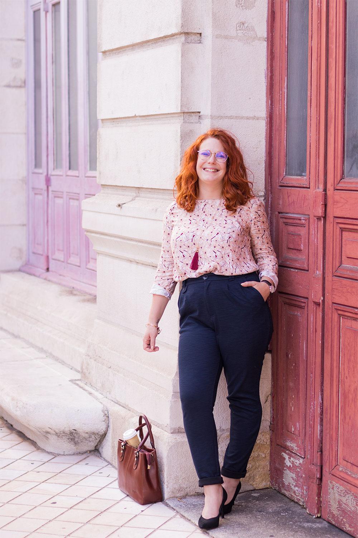 Le dos contre le mur en pierre blanc du grand théâtre de Tours, en blouse rose La Morue entrée dans le pantalon bleu marine Kiabi et escarpins noirs en velours