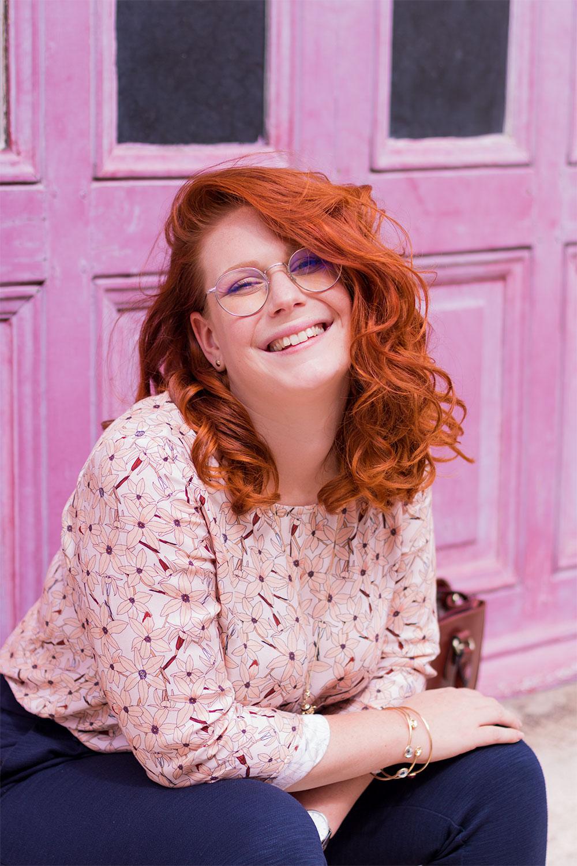 Portrait en blouse fluide rose La Morue, les cheveux énormément bouclés, devant une porte en bois rose fushia