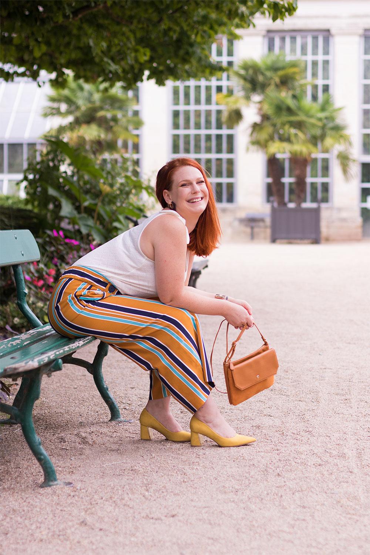 Assise sur un banc de profil avec les palmiers en arrière plan, en pantalon fluide et escarpins jaune à talons larges