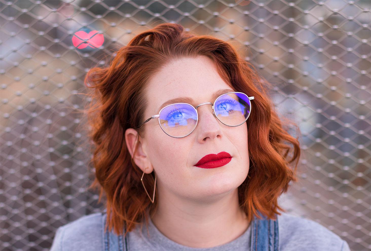 Lunette vintage et rouge à lèvres rouge, les cheveux bouclés, devant le grillage avec les lumières du train qui arrive