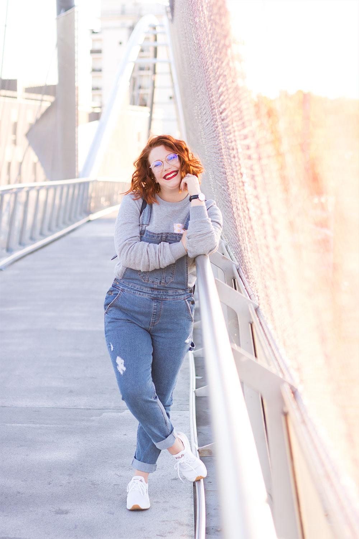 Accoudée à la passerelle en métal dessus des chemins de fer, en look street, salopette en jean et sweat gris