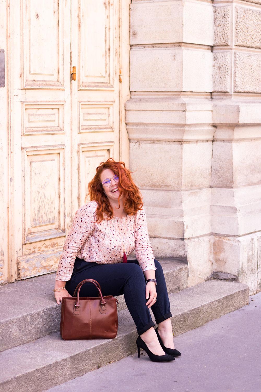 Assise sur les marches en bétons le long du grand théâtre de Tours, en pantalon cigarette bleu et blouse rose La Morue, pour la rentrée