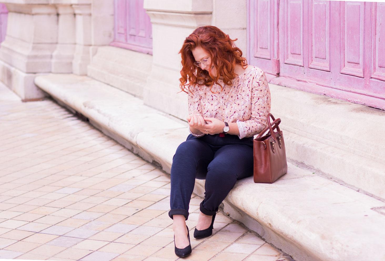 Assise de profil sur des marches en pierre devant deux grandes portes en bois fushia, en style working girl blouse et pantalon cigarette
