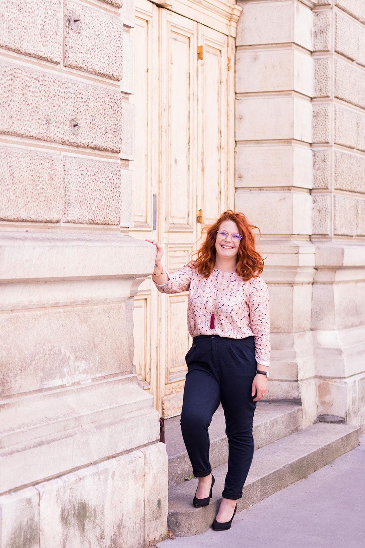 En working girl, blouse à fleurs roses et pantalon cigarette, le long d'un grand bâtiment en pierres blanches