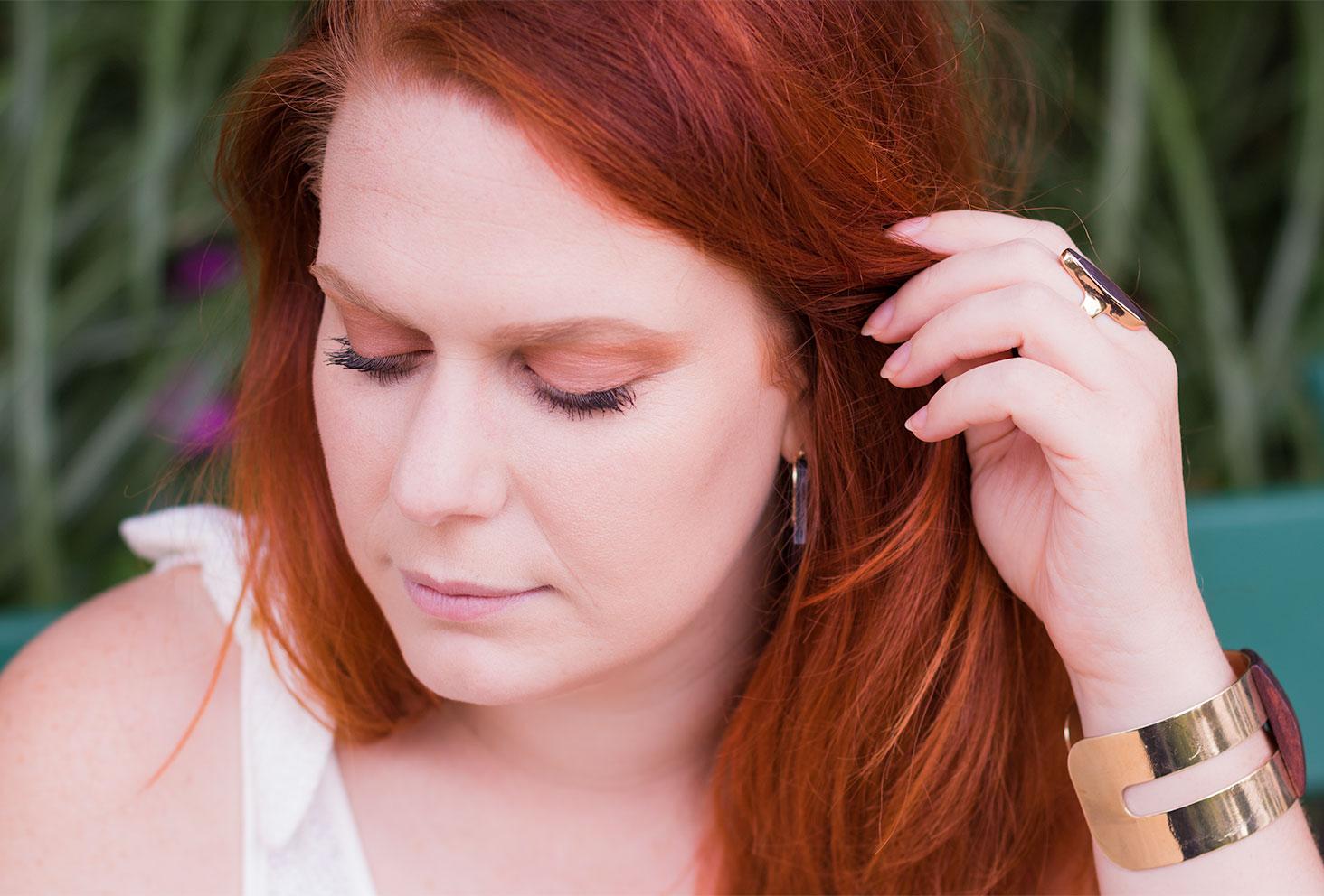 Zoom sur un make-up marron et doré, les yeux fermés et la main dans les cheveux roux