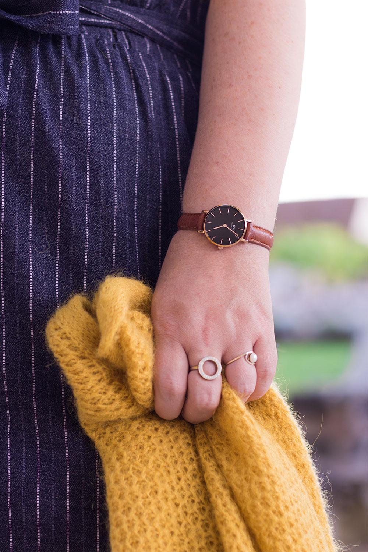 Zoom sur la Classic Petite portée de face devant une jupe bleue avec le gilet jaune dans la main